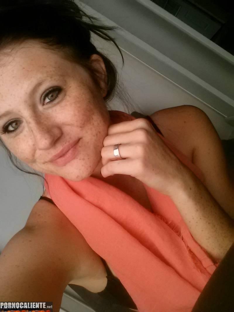 Pelirroja pecosa de ojos verdes haciéndose selfies eróticos